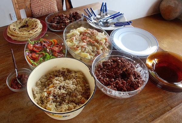 Alle Klassiker auf einem Tisch: Fleisch, Kartoffeln, Maharagwe (Bohnen), Pilau, Kachumbari (Salat) und Chapati (im Uhrzeigersinn)