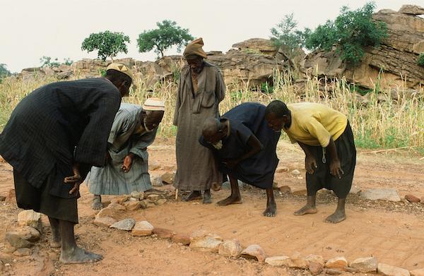 Die Dorfältesten beim morgendlichen Lesen von Tierspuren. Dazu wurde das Feld zuvor parzelliert, jeder Teil hat eine Bedeutung.
